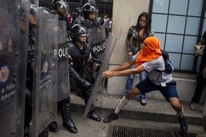 Protestors clash with police in Caracas in May. At least 43 people have died this year during anti-government rallies. Photographer: Miguel Gutierrez/Landov